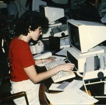 Image of 90's Student, Computing - Wearing a red t-shirt, white pants and eyeglasses, a young woman works at a computer in one of the computer classrooms or labs on campus.