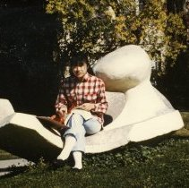 Image of 90's Student, Sculpture - Wearing a red and white plaid shirt and cuffed jeans, a young woman uses the white sculpture as a place to study.  She is sitting with a book lying across her lap and an open notebook next to her.  Part of Ackerman Hall is visible behind her.