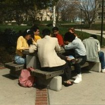 Image of 90's Students, Outdoors 1-1 - A group of foreign students sit outdoors at one of the stone picnic tables.  There is a partial view of Ackerman Hall in the upper right corner of the photo, and Inlow Hall is visible through the trees in the background.