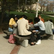 Image of 90's Students, Outdoors 1-2 - A group of foreign students sit outdoors at one of the stone picnic tables.  Inlow Hall is visible through the trees in the background.