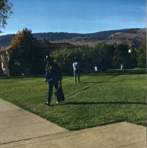 Image of 90's Students, Walking - Dressed in cowboy attire, a man walks on the grass across campus.  More students can be seen walking in the background.