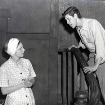 "Image of 1954-55 ""The Man"" 4 - ""Theater, 'The Man,' Roberta Miller, Jack Rye, 54-55""  In a scene from ""The Man,"" Jack Rye stands on a staircase and leans over the railing to talk to Roberta Miller who stands below.  He appears to be pleading or shouting at her, as she is looking at him askance.  She is wearing a plaid shirtdress with a kerchief on her head.  Her hands are clasped."