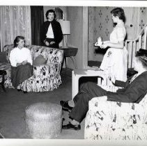 "Image of 1955-56 ""Time Out For Ginger"" 10 - ""Theater, Time Out For Ginger, 55-56""  In a livingroom scene from ""Time Out For Ginger,"" a man sits in a stuffed easy chair with an ottoman in front of him.  He is holding a pencil in his right hand.  Standing beside him is a woman holding a coffee set on a tray.  She is wearing an apron.  Seated on the couch that matches the chair in leaves and bamboo upholstery, is a woman in a long sleeved white blouse and patterned skirt.  Standing behind the couch is a woman in a dark skirt and sweater with a white blouse underneath."