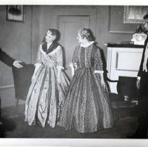 "Image of 1955-56 ""The Heiress"" - ""Theater, The Heiress, 1955-56""  In a well staged parlor scene from ""The Heiress,"" two women stand together with the two men at either sides of the room.  The women are wearing a long plantation era dresses, while the men have on short waist coats and string ties."