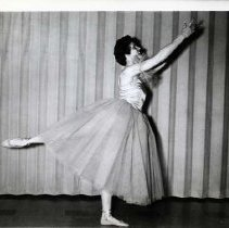 """Image of 1956-57 """"Sing Ho For a Prince"""" 1-1 - """"Jackie Shaw, 'Treakle' in Sing Ho For a Prince""""  Jackie Shaw poses flat on her left foot with her right foot extended out behind her, toe pointed.  Her hands are up in the air, and she is looking upward.  She is wearing a flowing tulle skirt with a satin bodice, tulle bands on her upper arms, and ballet shoes.  She has short, dark, curly hair"""