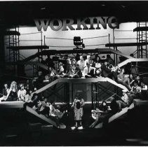 "Image of 90's ""Working"" - ""Working""  Performers fill a multiple platform staging during a production of ""Working"" in the Loso Hall Theatre.  They appear to be singing."