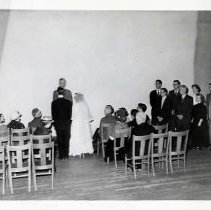 "Image of 60's Theatre, Stage Wedding - The scene is a couple getting married.  They stand before a minister, while people watch from seats on wooden chairs.  The chairs are set in two sections with an aisle down the middle.  To the right, six men and two women also view the ceremony.  The flooring is wooden slats, and the room is otherwise bare.  [Possibly, a scene from ""Our Town.""]