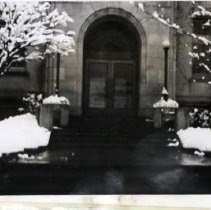 "Image of Ackerman School Entrance - ""Ackerman""  This is a picture of the entrance to Ackerman School.  Piles of snow sit on either side of the wet stairs, and the trees are frosted with snow."