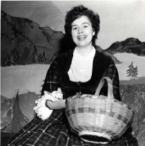 "Image of 1959 ""Brigadoon"" 1-1 - ""Sock and Buskin, Kay Hawk""  Dressed for the part of Fiona in 1959's ""Brigadoon,"" Kay Hawk sits on a stage rock while holding a basket."