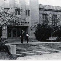 """Image of 70's Pierce Library Entrance - """"Walter M. Pierce Library""""  A young man and woman walk down the steps as they leave the Pierce Library.  They are both wearing long sleeves and pants for chillier weather.  On either side of the steps are leafless trees and evergreen shrubs."""