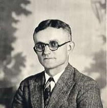 "Image of 1929 Alumni, George Overmeyer 1 - ""1929 - G. W. Overmeyer Jr. - First man to graduate from this school.""  This is a portrait of G. W. Overmeyer, Jr. wearing a tweed, suit jacket over a white, dress shirt and patterned necktie.  He is also wearing eyeglasses."