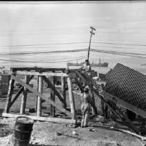 """Image of Biak Camp, Water Tank - """"Moving big water tank onto supporting frame - for gravity feed to Kitchen and showers.  Island of Biak - Dutch New Guinea 17th Tact. Recon Sqdn""""  From """"Darkroom Soldier"""":  """"Water Suppliers.  To create a gravity fed water supply for mess hall and showers, unidentified Utilities Section men winch a water tank up to its base.""""  (""""Darkroom Soldier"""" caption authored by George Venn)"""