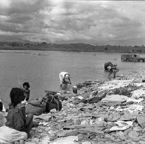 """Image of Mindoro, GI Laundry 1 - """"Filipino women (for most part) doing soldiers laundry in river""""  From """"Darkroom Soldier"""":  """" Busuanga River:  Upstream Bath, Downstream Laundry.  Hill reported these scenes to Martha:  'En route home, we stopped at the deep part of the river for a swim.  Couple of dozen men swimming.  Sign downstream reads, 'No Nude Bathing.'  I saw one pair of shorts.  Two hundred yards down the river, the Filipino women do GI laundry.""""  (""""Darkroom Soldier"""" caption authored by George Venn)"""