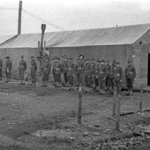 """Image of 186th Infantry, Formation - """"1st of  E Co. 186 Inf. at Fort Lewis - Camp Murray Tent area - 41st Div.  Row of men beside a building"""""""