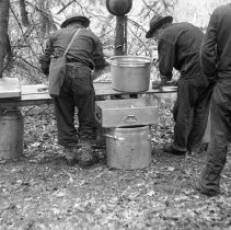 """Image of 186th Infantry, Field Kitchen 2 - """"E Co. 186th Infantry - Field exercises - Fort Lewis 1941 - field Kitchen - WW1 helmets"""""""