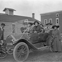 Image of Automobile, Day Ride 2 - Four women try out the seats in an automobile, while two men and a woman stand outside of the car admiring it.