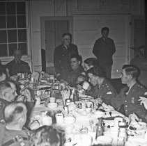 "Image of 41st Cantonment, Hosted Dinner 1 - ""On one occasion, E Co. 186 hosted a dinner for Battalion officers - at Cantonment Area - Seated at head of table in both pictures is Chaplain Capt Blenkinsop - Standing is E Co. Commander, Capt Jess Andrews plus an E.M. attendant"""