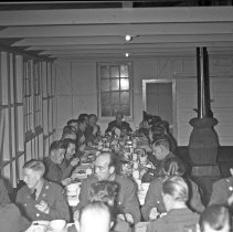 """Image of 41st Cantonment, Hosted Dinner 2 - """"On one occasion, E Co. 186 hosted a dinner for Battalion officers - at Cantonment Area - Seated at head of table in both pictures is Chaplain Capt Blenkinsop"""""""