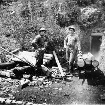 """Image of Baker, Standard Mines (copy) - """"Baker [County] area mines - Standard Mines - Two men at entrance of mine - Shows cribbing cut for mining tunnels piled near the entrance of the tunnel - circa 1901-1903""""  [Original:  2010.2.2171 - Glass-plate negative.  Copy:  2010.15.00502 - Photograph print]"""