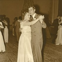 """Image of 1932 Dance, Christmas 2 - """"1932+/-  Christmas dance put on by the members of the Social Committee""""  Wearing formal attire, a couple dances together.  More couples dancing can be seen in the background, and streamers decorate the back wall."""