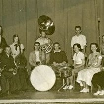 "Image of 1935 Band - ""1935+/- Band & Orchestra""  Holding their instruments, the EONS Band poses together indoors."