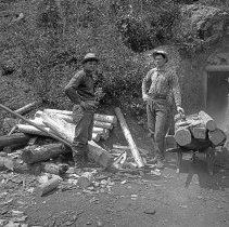 """Image of Baker, Standard Mines - """"Baker [County] area mines - Standard Mines - 2 men @ entrance of mine - Shows cribbing cut for mining tunnels piled near the entrance of the tunnel - circa 1901-1903""""  [Copies:  2010.2.1868 - Film negative, 2010.15.00502 - Photograph print]"""