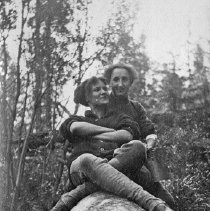 Image of Reuter, Women 2 - Two unidentified young women sit on a large log, one behind the other.  They are wearing pants and carrying pails.  Presumably, they have been up in the hills berry picking.