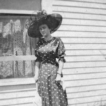 Image of Reuter, Woman 5 - Wearing a fancy hat and carrying a parasol and hankie, an unidentified, young woman poses for a picture next to the window of a house.