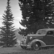"Image of Automobile, 1938 - ""1938 - Trip to Snake River Canyon?""  An automobile drives along a dirt road with evergreens and mountains in the background."