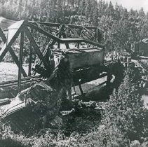 Image of Train Wreck, Bridge 2 - The wreckage of a train and twisted, steel girders of a railroad bridge after a derailment.