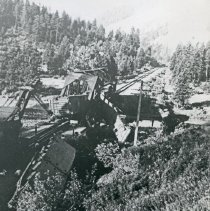 Image of Train Wreck, Bridge 3 - The wreckage of a train and twisted, steel girders of a railroad bridge after a derailment.