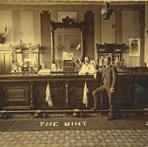 """Image of Elgin, The Mint Saloon - """"The Mint Saloon interior - J.B. Thorson in front of bar - C.L. Mellquist behind the bar - circa 1890's""""  [Note:  The many spittoons along the footrail in front of bar.]  [Labeled here as being in La Grande.  However, Fred Hill places The Mint Saloon in Elgin, Oregon on the southeast corner of Birch and 8th.]"""