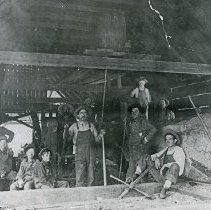 """Image of Elgin, Sawmill Crew - """"Elgin, Oregon - circa 1915""""  Sawmill crew with a very large tree they are working on, posing in the open-air sawing shed."""