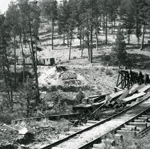 "Image of Train Tracks, Construction 1 - ""Sumpter Valley Railway - circa 1910-1915""  Work on an elevated, curved piece of railroad track appears to be ongoing.  Railroad ties are piled to the side, and there is a train of boxcars parked in the background."