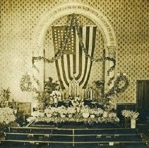 "Image of Floral Arrangements 1 - The interior of a church's chapel where the altar area as been decorated with an abundance of flowers.  [Note:  The American flag hanging on the wall behind the altar has 44 stars.] [The two small banners on the wall to each side of the flag read:  ""1852"" and ""1902.""  This is indicative of a 50th anniversary event.]"