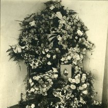 "Image of Floral Arrangements 2 - ""Arrangement of funeral flowers with a photograph of the deceased, an unidentified woman, circa 1900's.  One card with the arrangement reads:  From the Crucible State Normal School; Greely, Colo."""