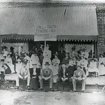 "Image of La Grande Group, July 4th - ""Fourth of July Celebration - La Grande, Oregon.  A group of people pose in front of Ralston Furniture and Undertakers.  The entrance for Williams Bros. Law Offices, which were on the second floor, is to the right.""  Identified in photograph:  ""1. Fan McWhirter, 2. Hat Kinsey, 3. Johnny Moran, 4. Mabel Williams, 5. Libby Kinsey, 6.-13. unidentified 14. Dr. R.J. Chipman, 15. Miss Anson, 16. Ira F. Powers, 17. Frederick L. Meyers, 18. Al V. Andrews.""  Mrs. Libby Kinsey is holding up a sign which reads:  ""Call and See Us.  Powers and Co. Furniture and Carpets.""  [Ben Weathers, who owned a print of the same photograph, noted the following information:  ""The picture was taken after 1890 and before 1896.  This building was on the east side of Depot Street just south of Adams Avenue, and the M.J. Berry store (later Newlin Drugs) was on the corner of Depot and Adams, just to the right of picture.  The Williams Law Office was in the building many years.""]"