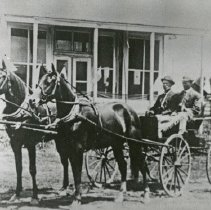 """Image of Elgin Men, Knight - """"Roy and Jesse Knight are sitting in their buggy in front of Ada Loshe's store, circa 1905.""""    [Photograph used in """"History of Elgin, Oregon"""" by Bernal Hug (page 108, picture no. 78).]"""