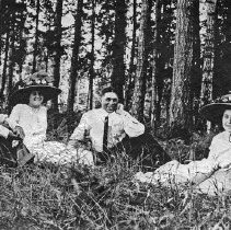 Image of Reuter Group, Small 5 - Walter Reuter (on the left) sits on the ground in the woods with two unidentified young women and a man.  The ladies are wearing fancy hats that are adorned with flowers.