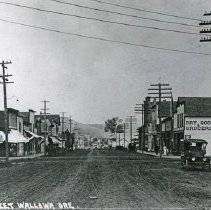 "Image of 1920+/- Wallowa, Main Street 1 - ""No. 38 Main Street Wallowa Ore.""  This picture depicts the unpaved Main Street in Wallowa, Oregon, circa 1920.  There is a ""Dry Goods and Groceries"" store on the right with an automobile parked near it, and the electrical poles are quite extensive."