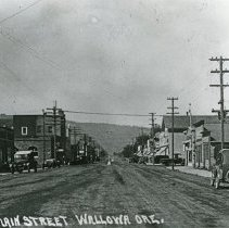 "Image of 1920+/- Wallowa, Main Street 2 - ""No. 2 Main Street Wallowa Ore.""  This picture depicts the unpaved Main Street in Wallowa, Oregon, circa 1920.  There are store fronts lining both sides of the street that look similar in architecture.  There are automobiles parked on both sides of the street, and the electrical poles are quite extensive."