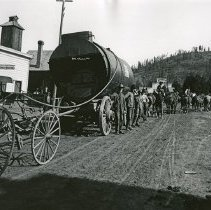 "Image of Baker, Midway Mines Boiler - ""Boiler for the Midway Mines Sinking Plant [Pleasant Valley, Baker County, Oregon] - circa 1901-1903.  It is riding on a wagon pulled by a 12-horse hitch.  Weight:  17,000 lbs.  There is a Dress Makers shop directly behind the wagons to the left, and the 'Eureka Stables' sign is just visible in the background."""