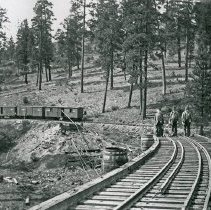 "Image of Train Tracks, Construction 2 - ""Sumpter Valley Railway - circa 1910-1915""  Work on an elevated, curved piece of railroad track appears to be ongoing.  Railroad ties are piled to the side, and there is a train of boxcars parked in the background."