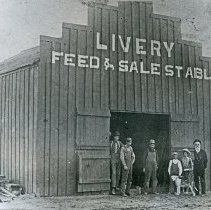 "Image of Wallowa, Livery Stable - ""Livery Feed & Sale Stable - Wallowa, Oregon (Wallowa County) - circa 1895-1900."" Notation on original photo:  ""Wallowa - later burned""  [""If so, it is not the same structure that burned September 1914 (owned by Nate Crowfut, operated by Johnson Hawley) and replaced by Morelock's Garage, that was subsequently built on the same site in 1915.  Later, two structures were on northwest corner of block with Gable facing north, and were on corner east of bank.  Replacement structure of 1915 is still standing in 1973.  Small building in this photo (c. 1895-1900) may have been enlarged and converted into the building that later burned, but as shown, it faces the wrong way.  Probably a competing establishment instead.  Perhaps that which stood on bank of mill race north of Main Street.""]"
