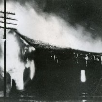 "Image of Wallowa Livery Stable, Fire - ""Wallowa Livery Stable - Burned, September 1914.  (First one built circa 1890.)  Owned by Nate Crowfut, operated by Johnson Hawley.  Gable faced north.  Building was located east of bank, on opposite corner.  It was replaced by the Morelock Garage building in 1915.  Its successor was owned by a Mr. McElroy and operated by Raleigh Rochester.  Was located on corner south of hardware and dry goods store and is still standing in 1973."""