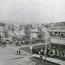 """Image of Enterprise, Elevated View - """"View of Enterprise public square before the courthouse or fairgrounds were built.  People are lined up on the sidewalks to get into the square where tents are set up.  Perhaps, a fair.  W.J. Funk & Co. is to the right of the public square."""""""