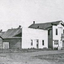 """Image of Elgin, Street Scene 1 - """"Street scene - east-side 7th Ave. S. between Division and Alder Sts. - Elgin, Oregon - June 16 to July 3, 1914 - From left to right: Jail [wood shack looking building], whorehouse [Large, white facade with two small windows on either side of the door.  Possibly closed by this time.], Barnes & Son Garage [Was originally the City Hall and Fire Station.  Also, the upstairs was often used for school classes. (It was built in 1898 by C.A. Raney, who contracted for the job in Sept. 1897.)  The last two buildings are not identified positively.]"""""""
