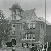 """Image of Elgin School - """"L.J. Carlson cut stone, began haul [with] 2 teams, Mon 4-27-08 (Jones Butte).  J.N. Roberts finished footings 4-28-08.  Slate Gen. Cont. starts super structure 4-30-08 to finish 9-15-08.  400 children [including] Elizabeth Galloway, age 12 years.  Board - J.T. Galloway, D.E.G. Kirby (Elgin, Ore.) and E.G. Bailey, prof. (N. Powder).  Girl in picture:  Bessie (Portland?)."""""""