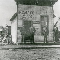 """Image of Elgin, R.C. Mays & Co. - """"'R.C. Mays & Co. Wholesale Grain Dealers' - picture before 1900.  Mays is the 2nd man from the left.  Looking west up alley from old Front St. just south of old Main St."""""""