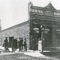 """Image of Elgin, M. & M. Co. - """"Milling & Mercantile Co. bldg. (stone warehouse) on the NW corner of 8th Ave. and Division St. - built in 1897.  Bed of Gordon Creek at the Galloway Mill Site, 3 mi. NW of town, donated stone for removal from Creek.  W.I. Dishman is tall man with black tie and G.W. (Buck?) is short man with black tie."""""""